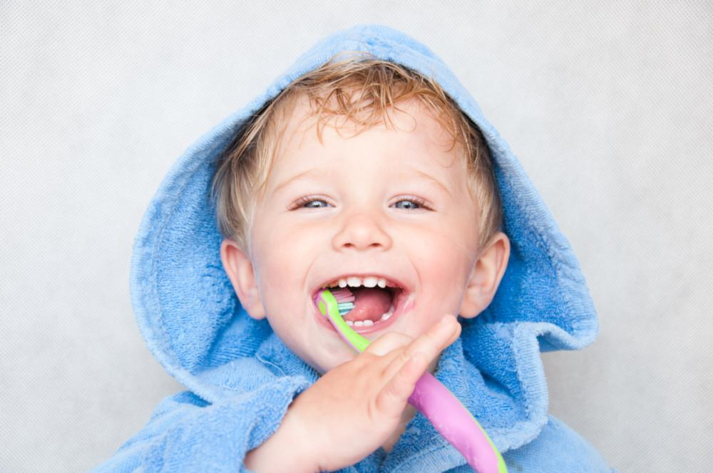 child smiling with toothbrush | family dentist jonesboro